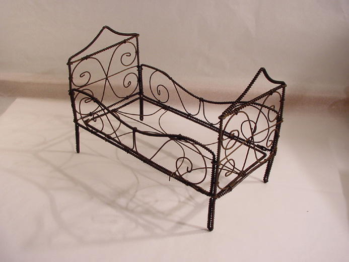 Doll's house furniture, a bed made from copper wire. [Click here to open image in popup]