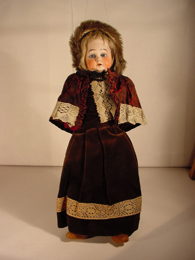 Doll wearing velvet dress and fur bonnet, around 1890. [Click here to open image in popup]