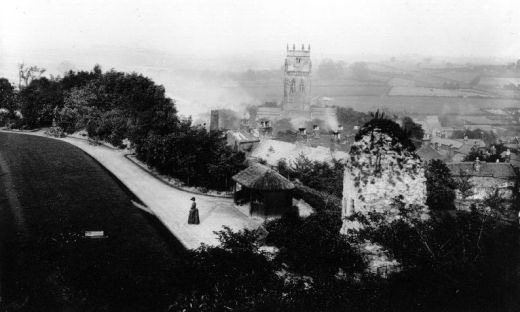 Looking south east from the top of the keep, over the Curtain Wall and the thatched predecessor to the 'Veteran's Shelter'. The visitor [a Carter from the Knottingley brewery] is wearing a dress which places the photo in the 1890s. Is that a croquet set on the lawn? [Click here to open image in popup]