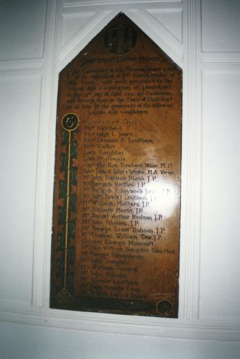 This inauguration plaque for the castle museum lists the benefactors. [An official emblem of the castle is at the top of this plaster plaque which has been 'grained' to look like wood] [Click here to open image in popup]