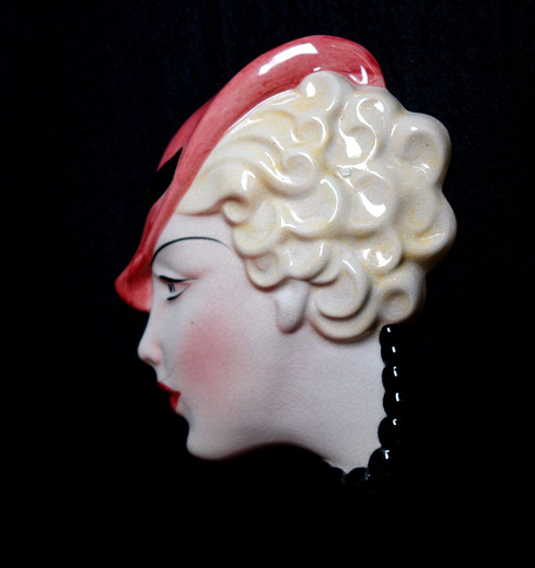Wall plaque in a Art Deco style, showing the face of a smart young woman with short blonde curls and a deep pink hat, made by Clokie and Co. in the 1930s. [Click here to open image in popup]