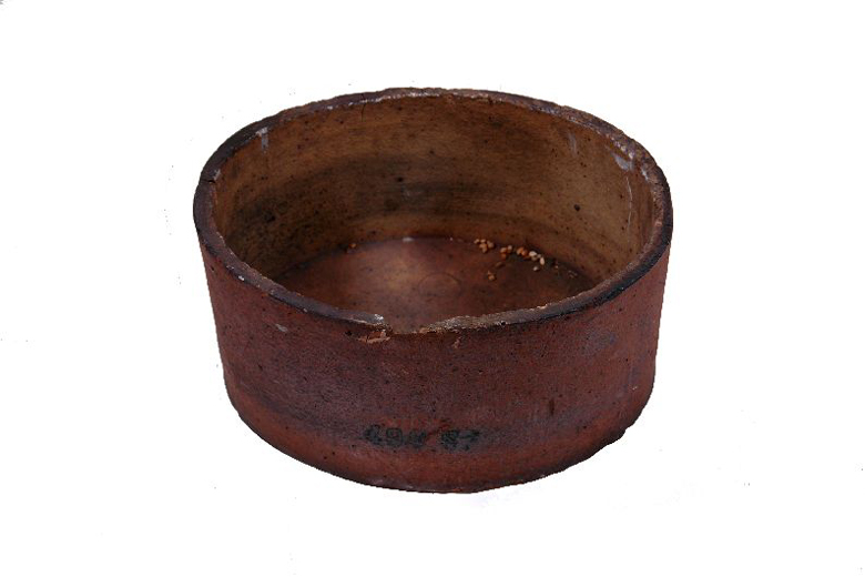 Saggar used to hold pottery during firing in the kiln, to protect the pots from direct heat. This saggar was collected from Clokie and Co. Ltd. after the pottery closed in 1961. [Click here to open image in popup]