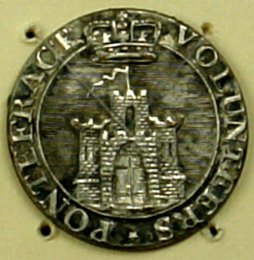 Silvered 19th century button of the Pontefract Volunteers which adapts one of the official emblems and adds a crown above. The tallest tower has an extra long narrow flag like the personal flags of, medieval monarchs [Click here to open image in popup]
