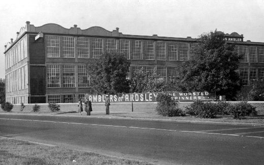 Black and white photograph of Ambler's worsted spinning mill in East Ardsley in 1953. The images shows a groups of four people standing in front of a banner which reads 'Amblers of Ardsley Fine Worsted Spinners…'. [Click here to open image in popup]