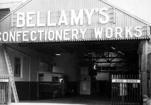 The image shows the loading bay at Joseph Bellamy & Sons Ltd confectionery works around 1960. In 1870 the company started manufacturing in Leeds, but in 1899 moved to Castleford.They became known for their mint imperials, French almonds as well as chocolate covered liquorice allsorts. In 1935 Joseph Bellamy & Sons Ltd became incorporated. The business was run in turn by the Bellamy family until it was taken over by John Mackintosh Ltd in early 1964. [Click here to open image in popup]