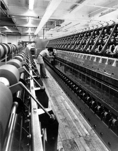 Black and white photograph of a female spinning operator at working at M.P. Stonehouse in Albion Mills in Wakefield in 1983. M.P. Stonehouse was worsted spinner founded in 1853 by Mathew Porritt Stonehouse and was based at Albion Mills in Wakefield. The factory's main focus was carding and spinning uncombed worsted yarn for carpets and for hand-knitting. [Click here to open image in popup]