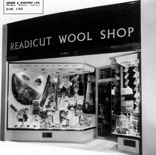 Black and white photograph of the Readicut Wool Shop c.1950. The photograph was produced by shop fitters Drake and Water Ltd. of Wakefield. The Readicut Wool Company was founded by Ralph Hirst in 1928 and was based a Terry Mills in Ossett. Hirst had the idea of supplying pre-cut wool which would save home rug makers the time and effort of carefully cutting yarn to size. In 2013 Readicut was still trading as part of the Orbital Group. [Click here to open image in popup]